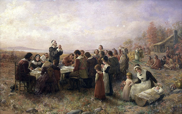 This is a painting of the First Thanksgiving at Plymouth. Pilgrims sit outside at a table praying over their meal. Native Americans sit on the ground in the background looking on. A mother rocks her baby in a wooden cradle as another young child stands beside her.